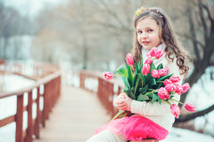 Spring portrait of happy child girl with tulips bouquet on the walk. Spring vertical portrait of beautiful child girl with tulips flowers on the walk stock images
