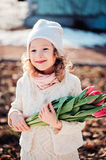Spring portrait of happy child girl with tulips bouquet for woman's day Royalty Free Stock Photo