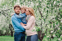 Spring portrait of happy family enjoying holidays in blooming garden Royalty Free Stock Images