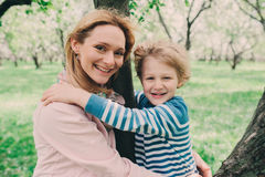 Spring portrait of happy pregnant mother enjoying warm day with child son Royalty Free Stock Photos