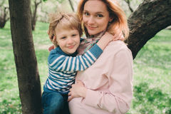 Spring portrait of happy pregnant mother enjoying warm day with child son Stock Photo