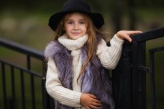 Spring portrait of a little girl.Sweet girl with big brown eyes in a black hat and a fur vest. stock photo