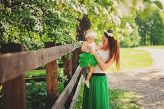 Spring portrait of mother and baby daughter playing outdoor in matching outfit - long skirts and shirts Royalty Free Stock Photography