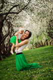 Spring portrait of mother and baby daughter playing outdoor in matching outfit - long skirts and shirts Stock Photo