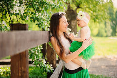 Spring portrait of mother and baby daughter playing outdoor in matching outfit - long skirts and shirts Stock Image