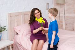 Spring portrait of mother and son on Mother`s Day. Cute boy and his mother at home. Son gives flowers to his beautiful mom, home interior. Woman`s day concept stock photo