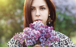 Spring portrait of a pretty woman holding a lilac flowers. Outdo royalty free stock photography