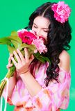 Spring portrait of a pretty young brunette smelling a bunch of g Royalty Free Stock Images