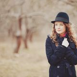 Spring portrait of red hair girl in hat and coat. Royalty Free Stock Images