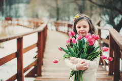 Spring portrait of smiling child girl with tulips bouquet on the walk Royalty Free Stock Images