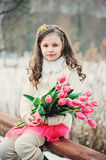 Spring portrait of smiling child girl with tulips bouquet on the walk Royalty Free Stock Photography