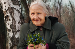 Spring portrait. Of the smiling elderly woman, in a forest with spring flowers Royalty Free Stock Photo