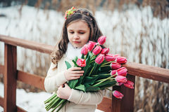 Spring portrait of thoughfull child girl with tulips bouquet on the walk. Spring portrait of thoughfull child girl with pink tulips bouquet on the walk royalty free stock image