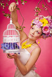 Spring portrait woman with a birdcage and flowers Royalty Free Stock Photos