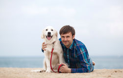Spring portrait of a young man with a dog on the beach stock photo
