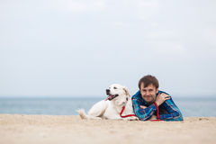 Spring portrait of a young man with a dog on the beach stock images