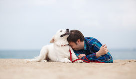 Spring portrait of a young man with a dog on the beach. A nice young man, with a fashionable hairstyle and brown eyes, wearing a blue plaid shirt, spends time on Royalty Free Stock Photography