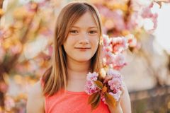 Outdoor fashion portrait of cute preteen girl. Spring portrait of young preteen kid girl with pink blooming flowers Stock Images