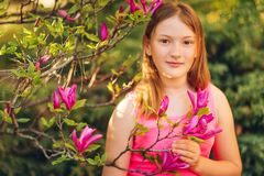 Outdoor fashion portrait of cute preteen girl. Spring portrait of young preteen kid girl with pink blooming flowers Stock Photography