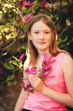 Outdoor fashion portrait of cute preteen girl. Spring portrait of young preteen kid girl with pink blooming flowers Royalty Free Stock Images
