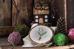 Spring postcard with cross stitched snowdrop on the wooden background. royalty free stock photography