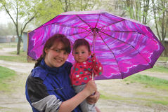 Spring rain is mother with daughter standing under an umbrella Stock Image