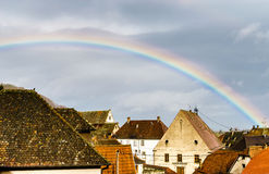 Spring rain and rainbow over little french village Stock Images