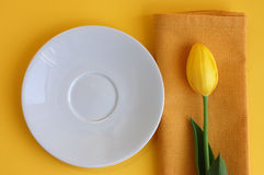 Spring Refreshment. White plate and a yellow tulip on a napkin Royalty Free Stock Image