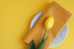 Spring Refreshment. Yellow tulip and a napkin on a white plate on a yellow background Royalty Free Stock Photo