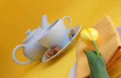 Spring Refreshment. A cup of tea with brown sugar cubes, a tea pot, yellow tulip and a napkin on a plate on a yellow background Royalty Free Stock Images