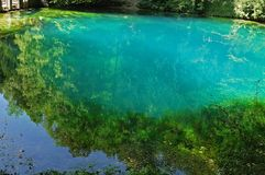 Spring of river Blau in Blaubeuren, Germany. Blautopf, karstic spring, source of river Blau in Blaubeuren, Germany, with turquoise water royalty free stock photo