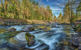 Snoqualmie River in the Cascade Mountains during. Slow Shutter on a Sunny Day creates Silky Washington State Mountain River Stock Photography