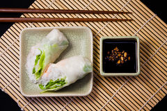 Spring roll and soy sauce. Spring roll, chopsticks and soy sauce on a bamboo mat Royalty Free Stock Photos