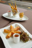 Spring rolls and chicken satay plates. Spring rolls on a plate with a chicken satay plate in the background on a resort at Lamay, Koh Samui in Thailand Stock Photos