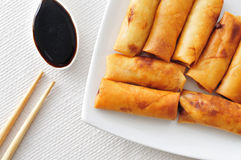 Spring rolls. Closeup of a plate with some spring rolls on a set table with a bowl with soy sauce and a pair of wooden chopsticks Royalty Free Stock Photo