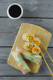 Spring rolls. Portion of spring rolls on a bamboo board with smoked salmon, carrot and cucumber Stock Images