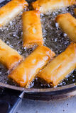 Spring rolls with prawns being fried. Stock Images