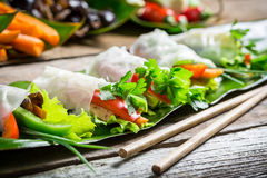 Spring rolls with vegetables and chicken. On old wooden table stock image