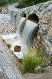 Spring Runoff. From a mountain river flows beneath a scenic roadway Stock Image