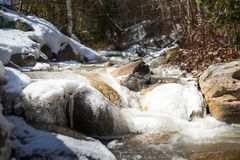 A creek runs past ice and snow covered boulders stock images