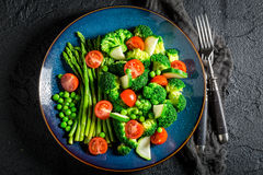 Spring salad with broccoli, asparagus and cherry tomatoes. On black rock Royalty Free Stock Photo