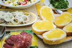 Spring salad with eggs, cucumbers and radishes, herring with onions and chopped sausage stand on the table. Useful and tasty lunch stock photo
