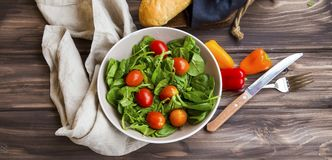 Spring salad with fresh green rocket, spinach leaves and cherry. Tomatoes , top view Stock Images