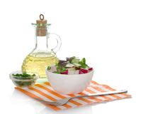 Spring salad with radishes and cucumber. Jug of sunflower oil, salad in a bowl and a fork on a napkin isolated on white Royalty Free Stock Photos