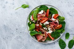Spring Salad with spinach, cherry tomato, mozzarella, pine nuts and ham with olive oil in a simple ceramic plate. On an old concrete gray background royalty free stock image