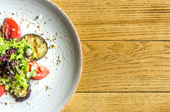 Spring salad: tomatoes, zucchini and herbs, on a white plate, on a wooden table Stock Image