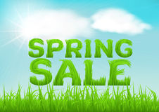 Spring sale inscription made of grass. Spring background with green early spring grass on blurred soft background. Spring outlet, clearance, seasonal sale Royalty Free Stock Images