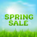 Spring sale inscription made of grass. Spring background with green early spring grass on blurred soft background. Royalty Free Stock Photography