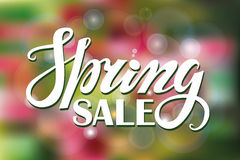 Spring sale.Lettering on Green,pink blurred background Stock Image