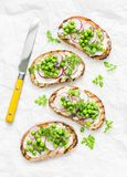Spring sandwiches - grilled bread, cream cheese, green peas, radishes and micro greens. Healthy eating, slimming, diet lifestyle c stock photo